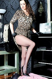 Sexy Mistress in leopard print dress wants her gimp to feel her full weight on his head.