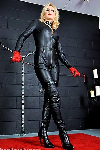 Leather clad domme torments cringing slave in the dungeon