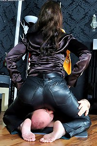 Mistress in leather trousers sits firmly over veteran slaveboy face